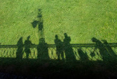 Shadows. People shadows on the grass royalty free stock images