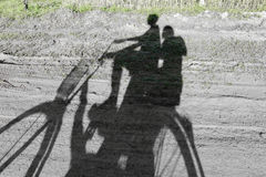 Shadows of people riding bicycle Stock Images