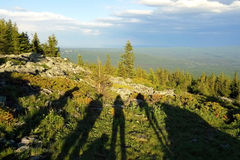 The shadows with the people on the view on the mountains, forest and cloudy sky. Travel to Ural mountains, Russia. The shadows with the people on the view on Royalty Free Stock Photos