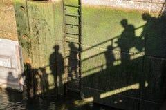 Shadows of people walking on bridge. Shadows of people walking on the walkway across the locks at the Ballard Locks Royalty Free Stock Photos