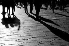 Shadows of people walking in the city. Shadows of people walking outdoors in a sunny city square Royalty Free Stock Photo