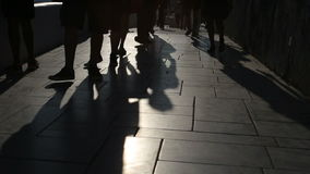 Shadows of people walking in city. Street procession