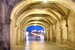 Shadows of people walking at night under ancient medieval loggia. S Royalty Free Stock Images