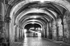 Shadows of people walking at night under ancient medieval loggia. S Stock Image