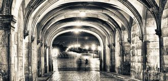 Shadows of people walking at night under ancient medieval loggia. S Stock Images