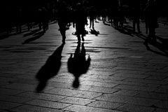 Shadows of people walking in the city. Shadows of people walking in an open square in the city center Stock Photo
