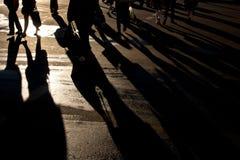 Shadows of people walking street. In morning light Royalty Free Stock Image
