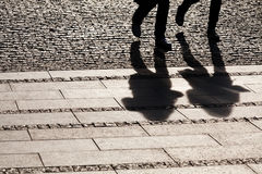 Shadows of people walking. On the street Stock Photo
