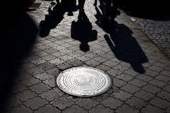 Shadows of people walking street i. N morning light Royalty Free Stock Images