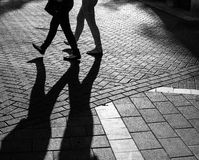 Shadows of people walking street. In morning light Royalty Free Stock Images
