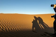 Shadows of photographers. Reflected on orange dunes of Hidden Vlei, Sossusvlie Namibia royalty free stock photo