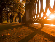 Shadows on the promenade. Autumn sunset on the embankment with people. Stock Photos