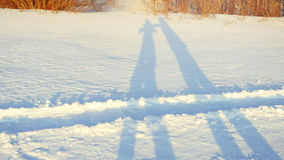 Shadows of romantic couple hiking on snow in winter sunny day during sunset time Royalty Free Stock Photography