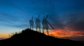 Shadows of Salvation. Cross getting carried up a hill at sunet royalty free stock photos