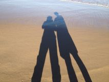 Shadows in the Sand. Shadows of a Couple in the Sand on a Deserted Beach Stock Images