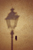 Shadows silhouette of street light at sunset on the wall Stock Image