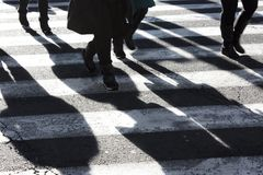 Shadows and silhouettes of people crossing the street stock image