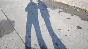 Shadows or silhouettes of two walking men on concrete slab road. Two silhouettes or shadows of two walking people on a road made of concrete slabs in a sunny day stock footage