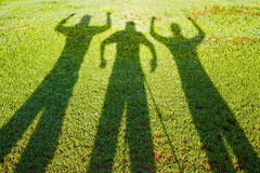 Shadows from three people on a grass Stock Photo