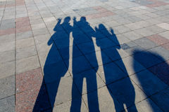 The shadows of three people on a pavement tiles Stock Photography