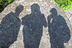 Shadows of three people. On a rock during a hike Royalty Free Stock Photo