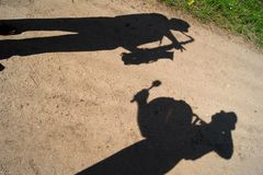 Shadows of two musicians. On a sandy road Stock Photos