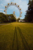 Shadows of the two people on the grass against the ferris wheel in the park in Vienna, Austria Royalty Free Stock Images