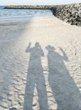 Shadows of two people on the sandy seashore stock images
