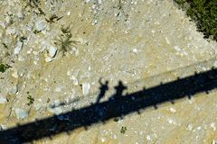 Shadows of two persons on the dry river bed under a suspension bride Stock Image
