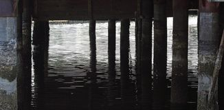 Under The Pier. Shadows under the pier in morning sun Stock Images