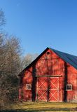 Shadowy Barn. A beautiful red barn with the shadows of the trees cast across its front in the evening sun Stock Photography