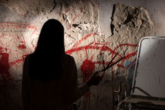 Shadowy female figure holding iron scissors near blood stained w Royalty Free Stock Images