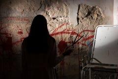 Shadowy female figure holding large iron scissors near blood sta Royalty Free Stock Image