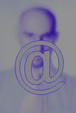Shadowy figure behind @ sign. Shadowy figure of a man behind the @ symbol to illustrate the anonymity of the internet Royalty Free Stock Images