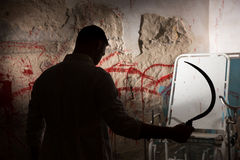 Shadowy figure holding sickle in front blood stained wall Royalty Free Stock Photos