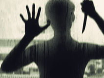 Shadowy figure with a knife behind glass Stock Photo
