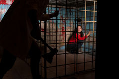 Shadowy male figure holding an ax in front of afraid female vict. Im imprisoned in a metal cage with a blood splattered wall behind her sitting in terror Stock Photography