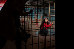 Shadowy male figure holding an ax in front of afraid victim impr. Isoned in a metal cage with a blood splattered wall behind her sitting in terror awaiting a Royalty Free Stock Photography