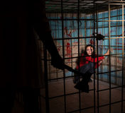 Shadowy male figure holding an ax in front of female victim impr. Isoned in a metal cage with a blood splattered wall behind her sitting in terror awaiting a Royalty Free Stock Image