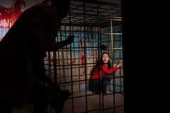 Shadowy male figure holding an ax in front of frightened female. Victim imprisoned in a metal cage with a blood splattered wall behind her sitting in terror Royalty Free Stock Photography