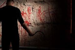Shadowy male figure holding sickle near blood stained wall Royalty Free Stock Photography