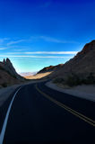Shadowy mountain drive. A shadowy drive into a brilliant blue sky Royalty Free Stock Images