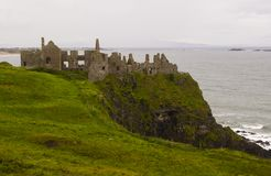 The shadowy  ruins of the medieval Irish Dunluce Castle on the cliff top overlooking the Atlantic Ocean in Ireland. The shadowy ruins of the medieval Irish Royalty Free Stock Photos