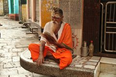A shadu of Benarés reads a book in front of his house. The sadhu is a holy man of the Hindu religion belonging to the caste of Brahmins. The caste of Stock Photography