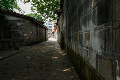 Shady alley between ancient dwelling houses in sunny summer Royalty Free Stock Photography