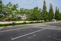 Shady asphalt road before old-fashioned enclosure in sunny summe Royalty Free Stock Photo