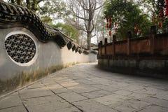 Shady flagstone pavement between aged enclosure and balustrade i Stock Photos