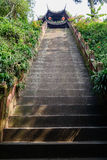 Shady hillsdie steep steps before ancient Chinese tower on sunny Stock Image