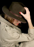 Shady Lady. A beautiful, mysterious woman in a trenchcoat and fedora hat, turned away so her face is hidden Royalty Free Stock Images
