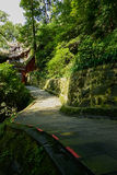 Shady lichen-covered stone path to ancient building on mountains. Shady lichen-covered stone path to an ancient Chinese building on woody mountainside in sunny Stock Photography